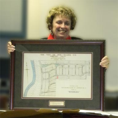 Mary Jo Cusack, Village of Riverlea holding framed plat